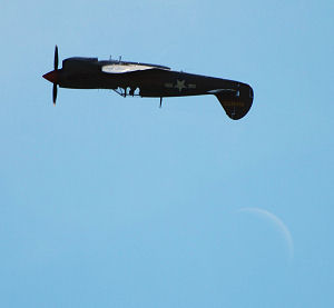 Photograph by Mike Bryant of a Curtiss P-40M Kittyhawk and the 3-day old Moon on 23/08/2009 at Bournemouth Airshow, Dorset, UK